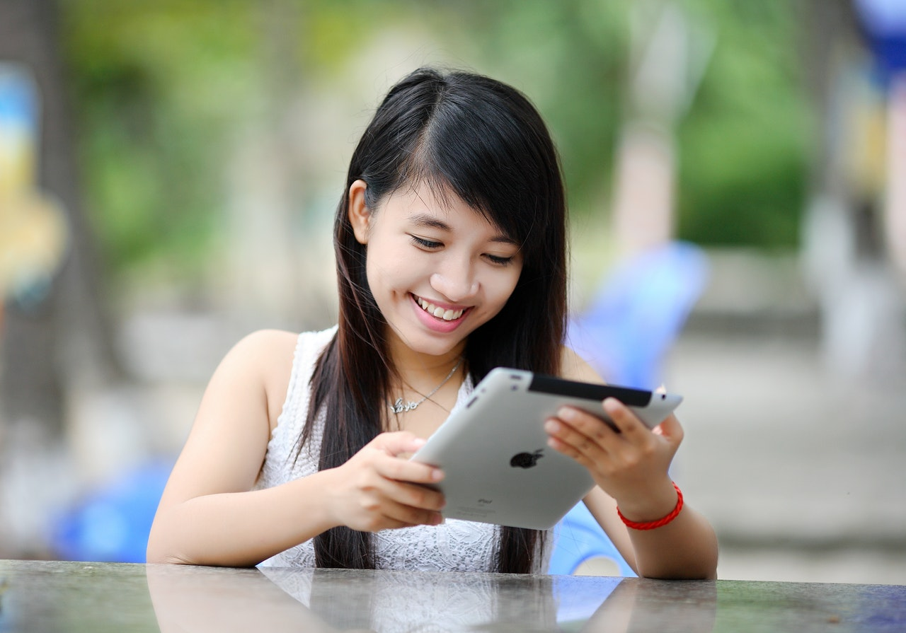 woman using apple tablet outdoors