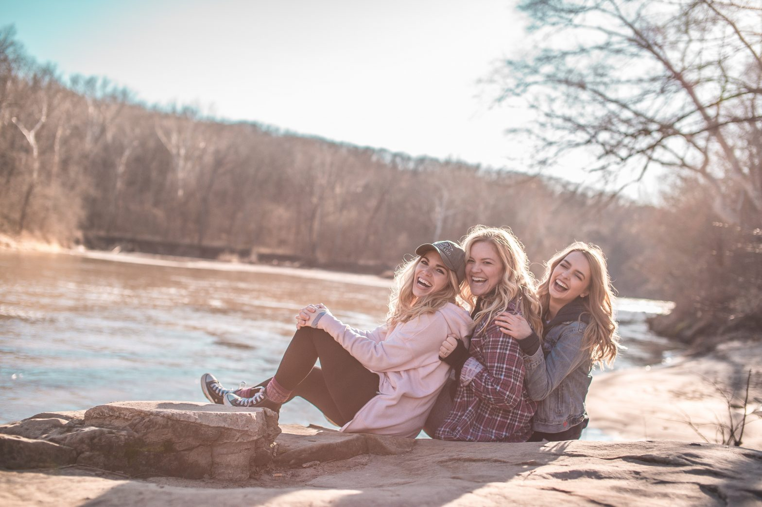 three friends enjoying life by a river in the winter sun