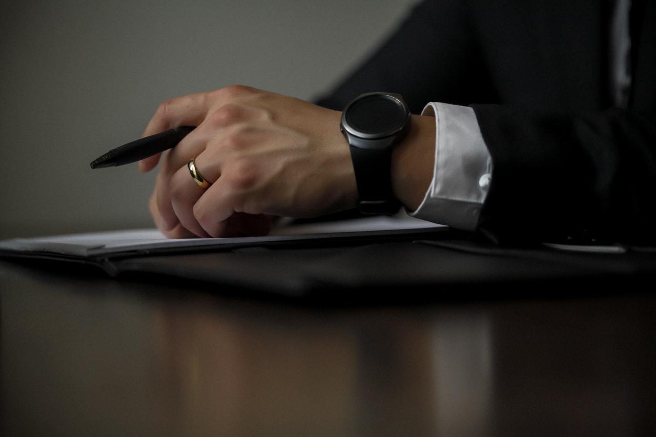 a man's hand holding a pen