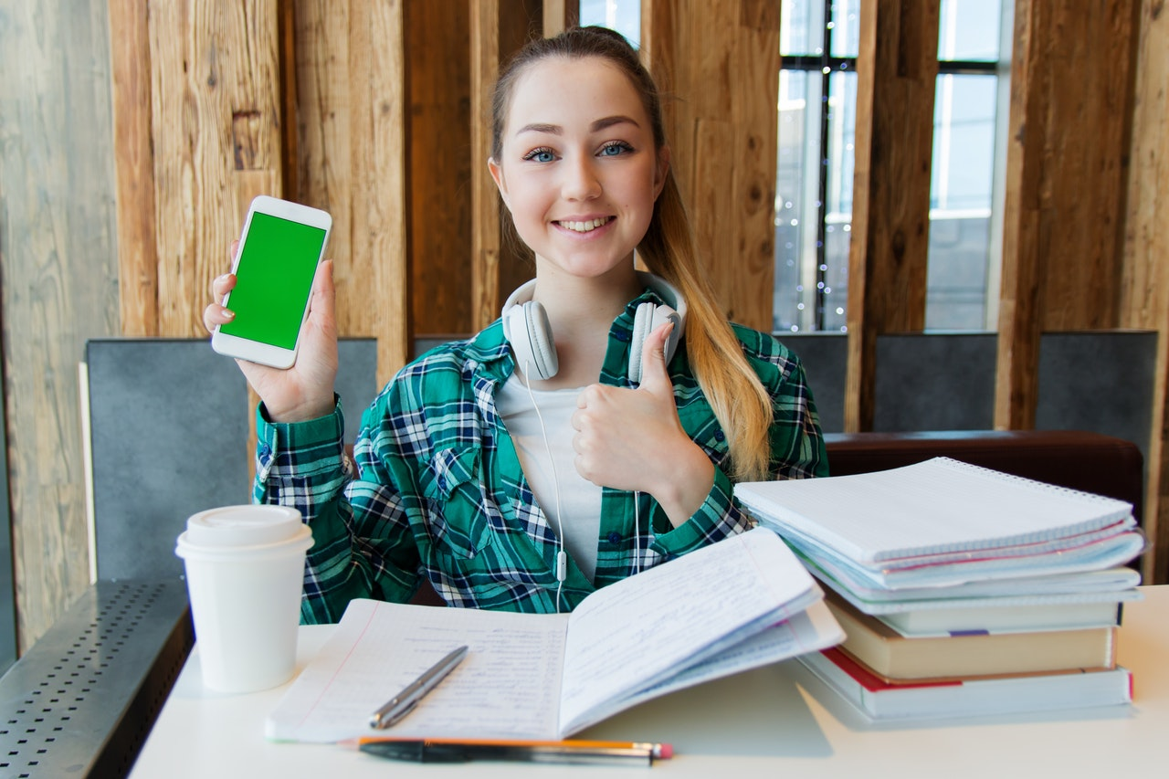 A woman with books carrying a phone.